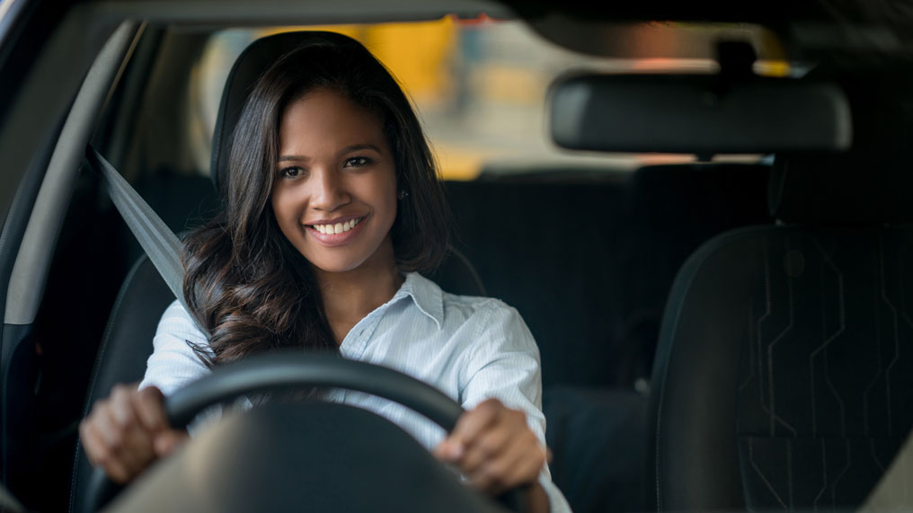 a woman smiles behind the wheel of her new car