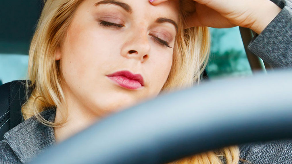 woman at steering wheel with eyes closed
