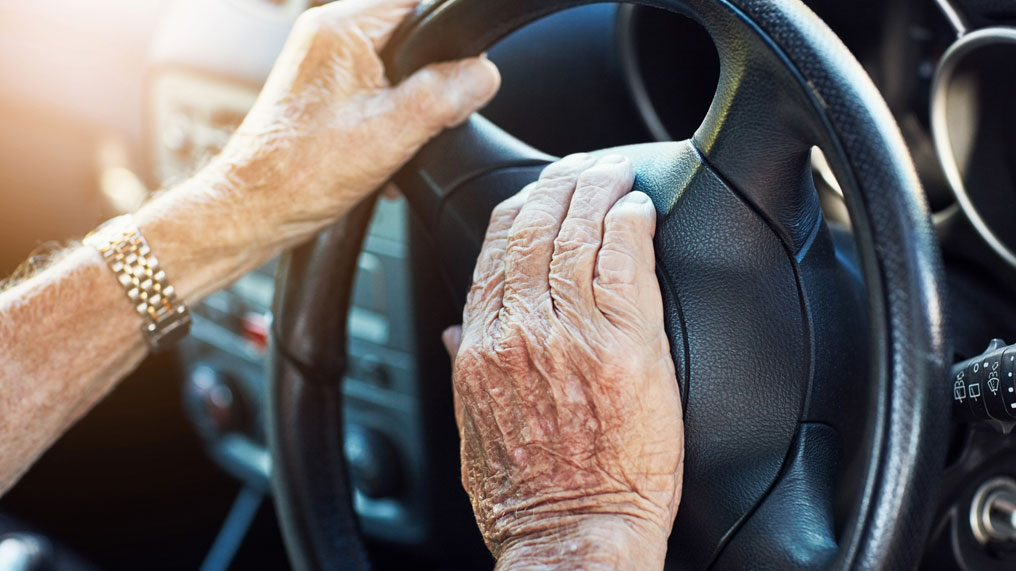 Older person's hands on steering wheel.
