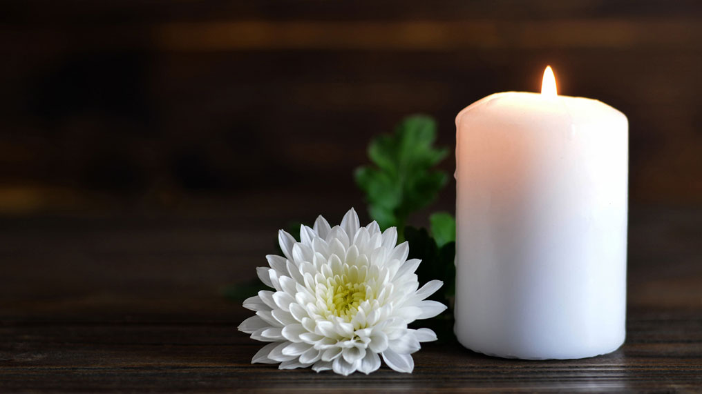 a candle burns next to a flower