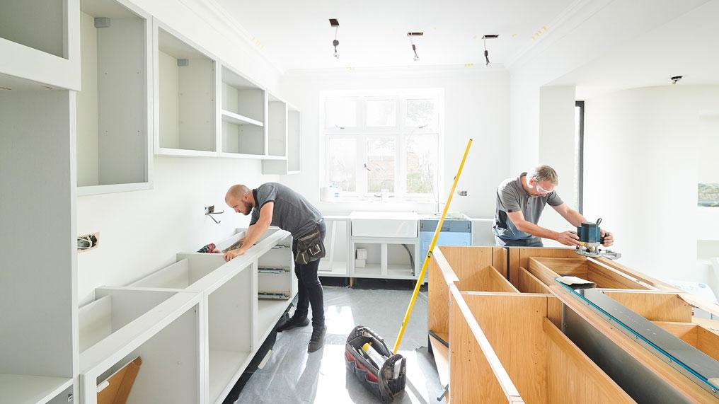 Tradesmen install a new kitchen.