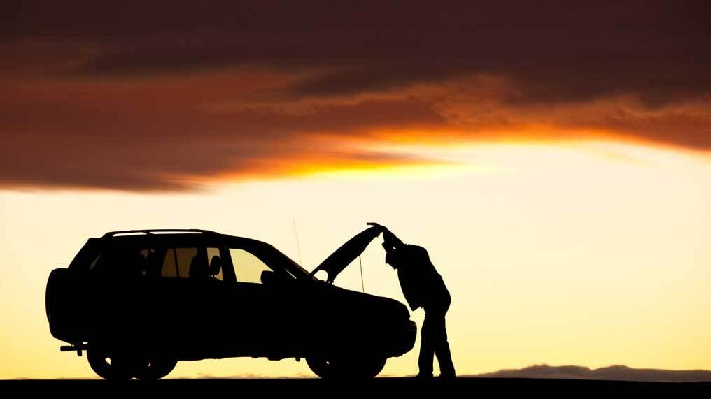 A driver looks under the bonnet of a broken down car.
