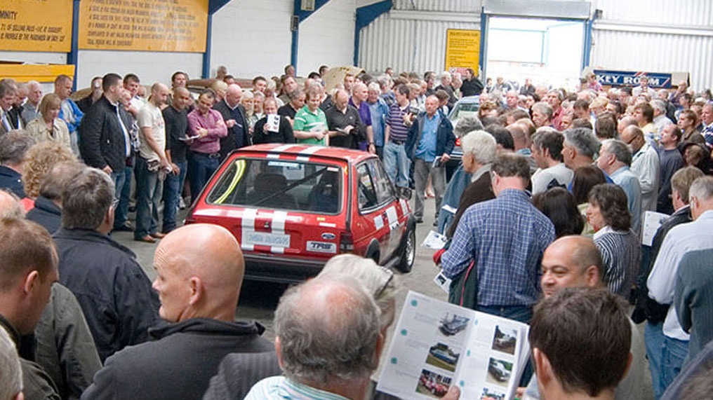 a crowd of people surround a car at auction