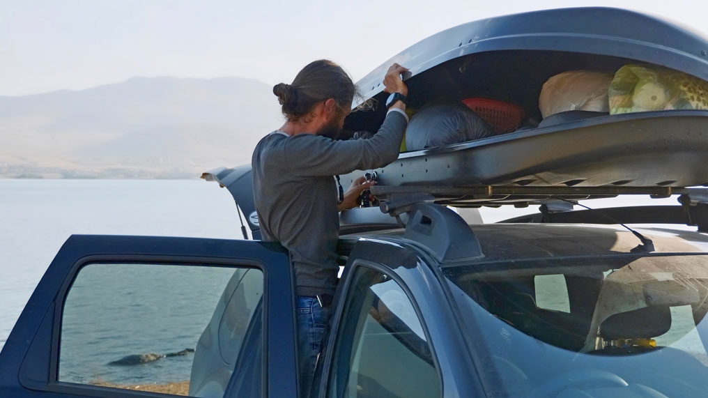 a man opens the roof box which is fitted to the top of a car