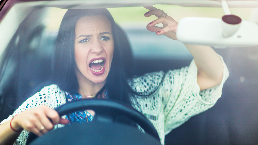 a woman gets angry behind the wheel of her car