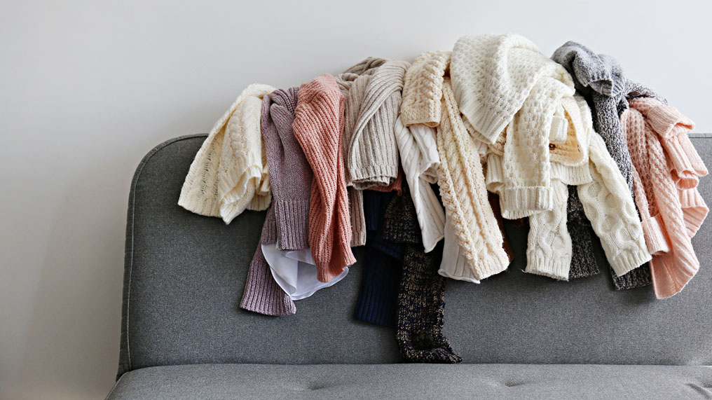 A pile of clothes are on the back of a sofa.