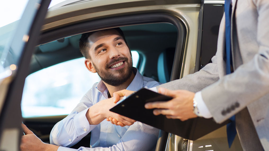 a man shakes a dealer's hand after buying a car