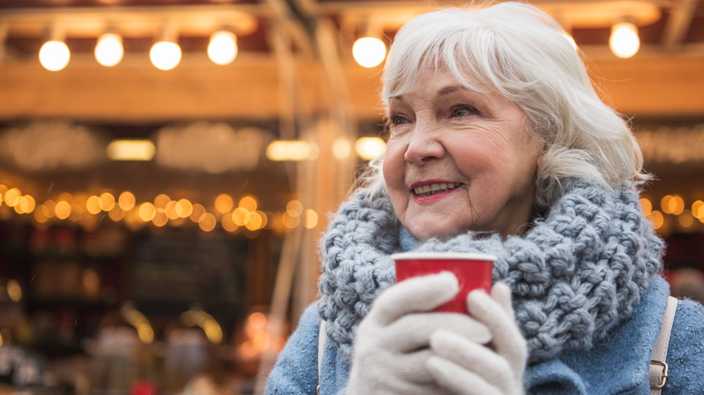 elderly woman holds a hot drink