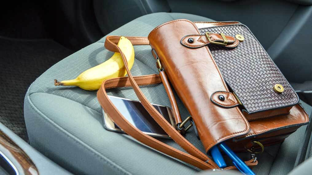 Personal possessions, including a phone and bag, have been left on a car seat.