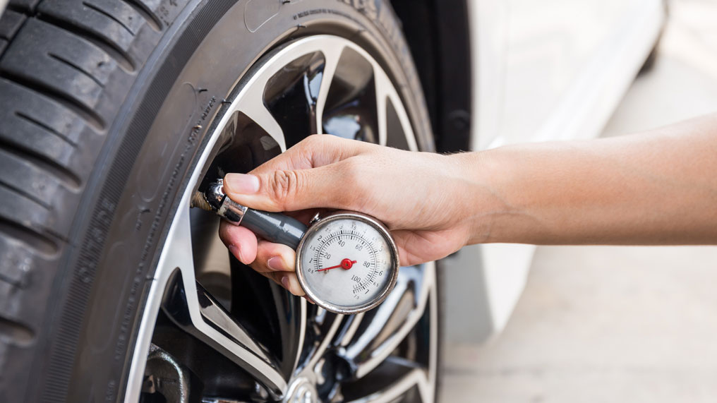 a person checks the tyre pressure