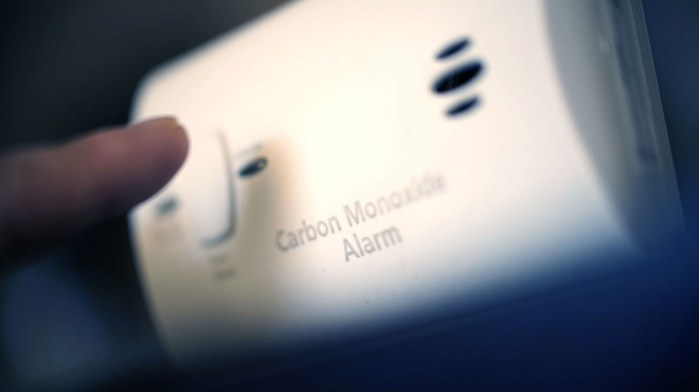 A person presses a button on a carbon monoxide alarm.