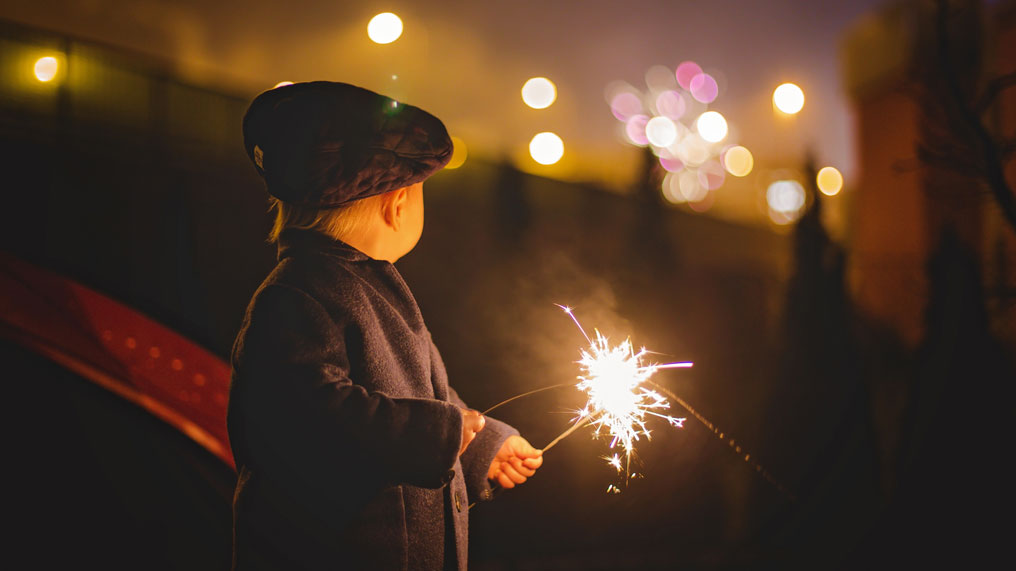 A child holds a sparkler during a firework display