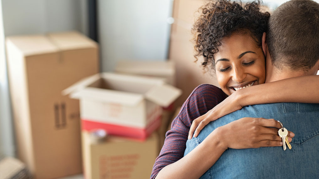a couple with packing boxes hug in their new home