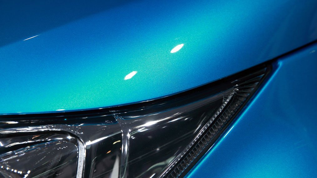 a car with a shiny coat of metallic blue paint