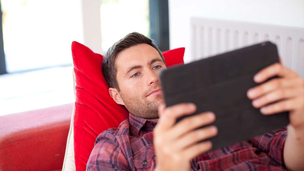 a man uses a tablet while lying on a sofa