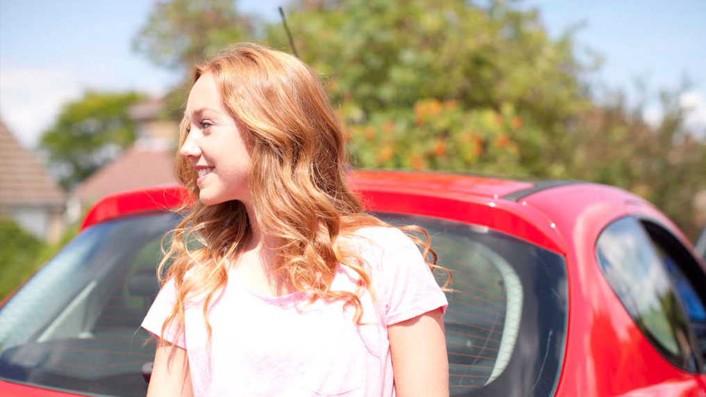a young woman stands by a red car