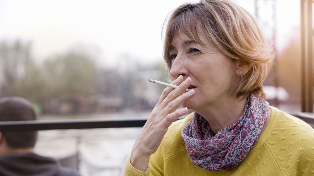 a woman in a yellow top smokes a cigarette.
