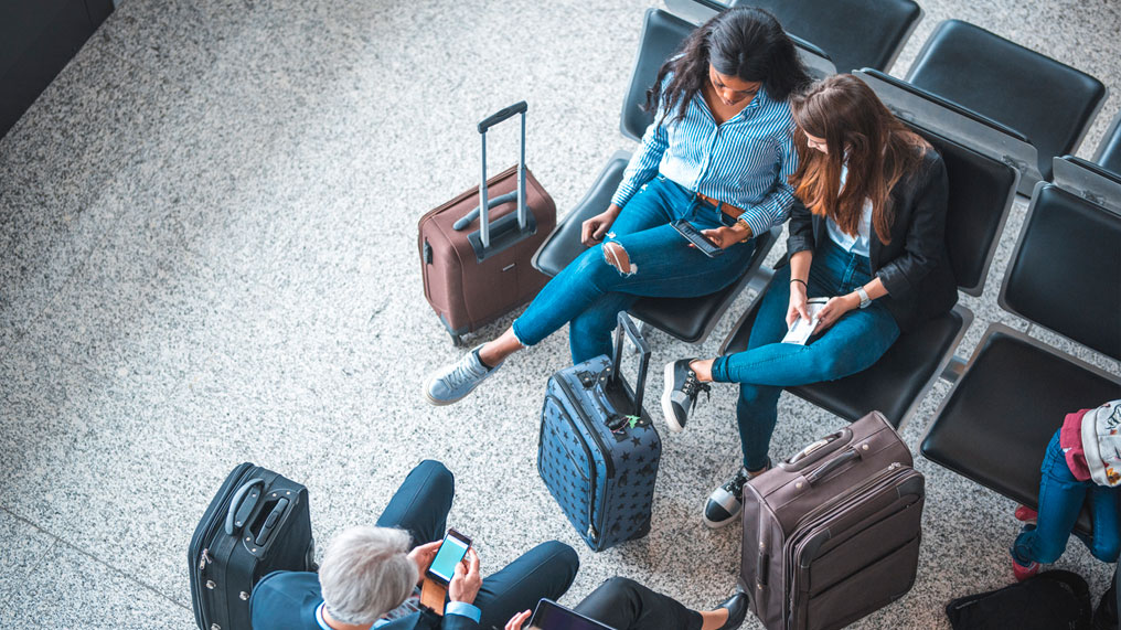 People sat at an airport with luggage.