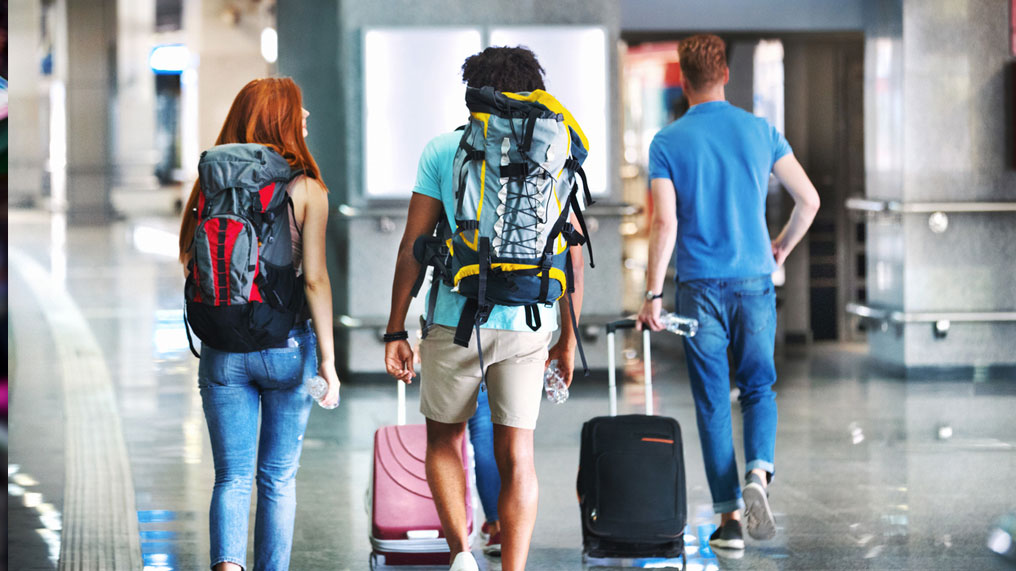 Three young adults walk through an airport.