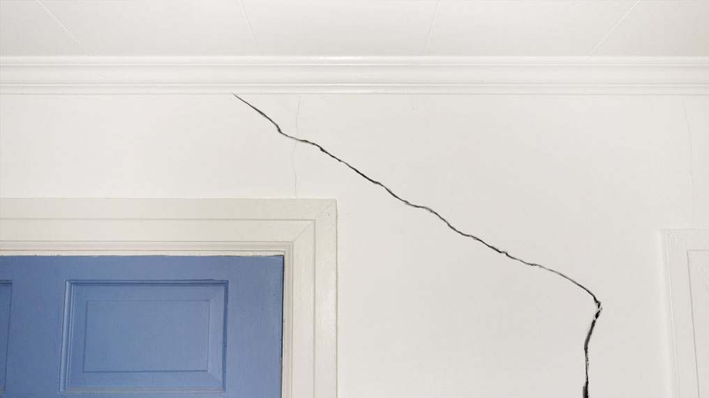 A large crack in a house wall
