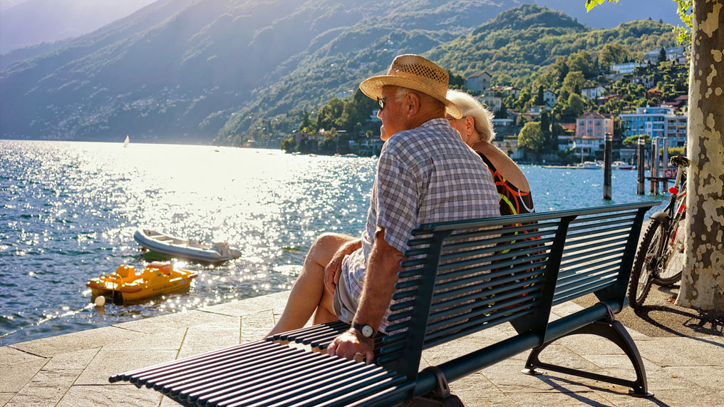 An elderly couple sit on a bench and look out over a lake.