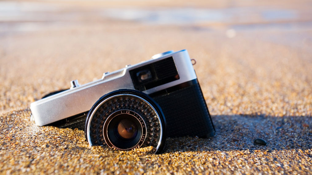 A camera partially buried in some sand.