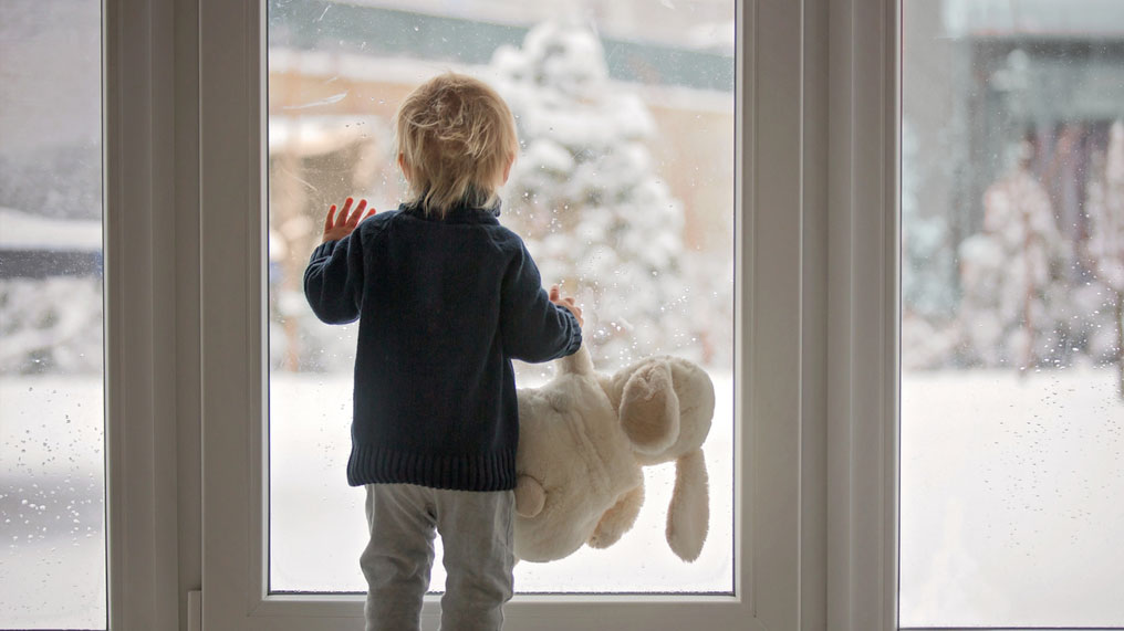 A child holding a soft toy looks out at a snow-covered garden.