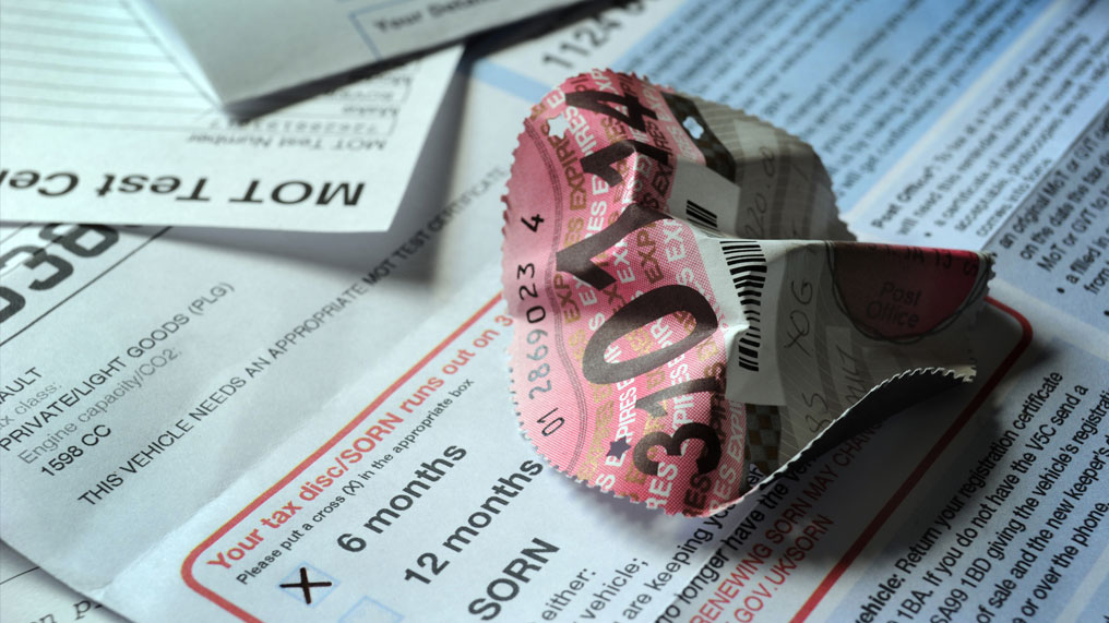 An old tax disc is crumpled on top of a road tax letter