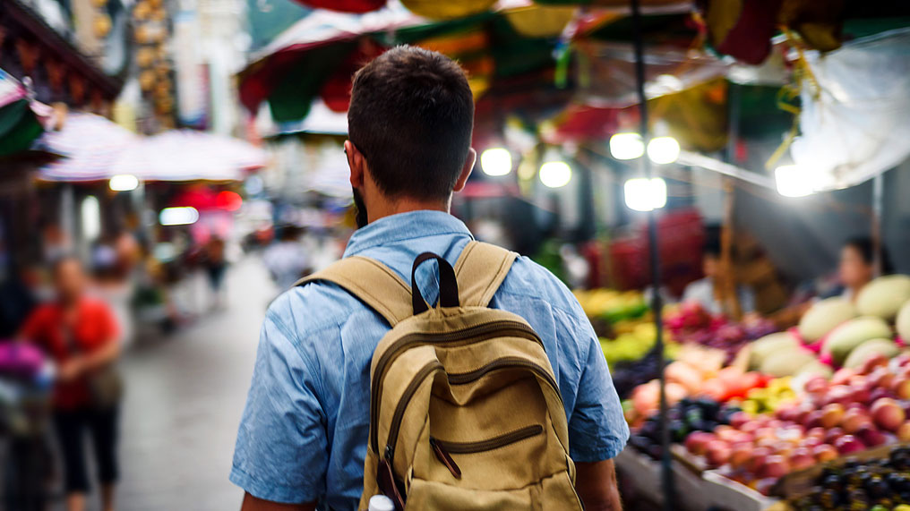 A backpacker walks through a street market.