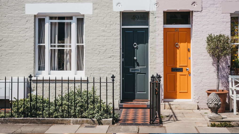 a home with a green door is next to a home with an orange door