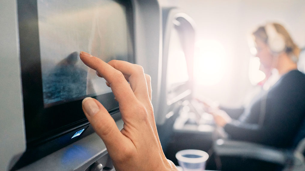 A passenger on a plane uses a screen to keep busy.
