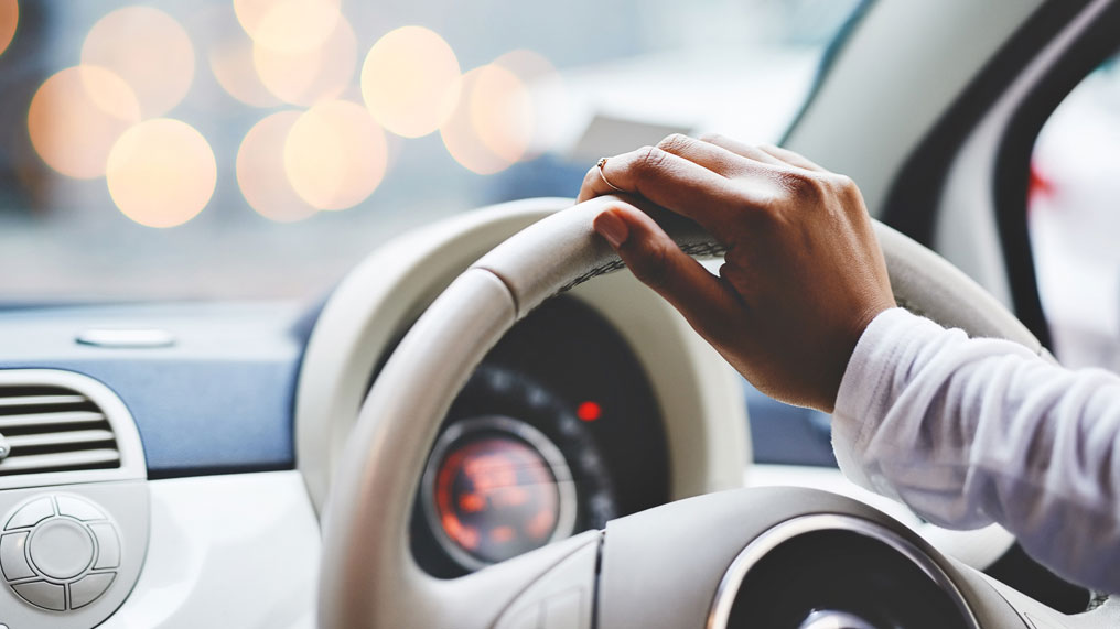 a driver has one hand on the wheel