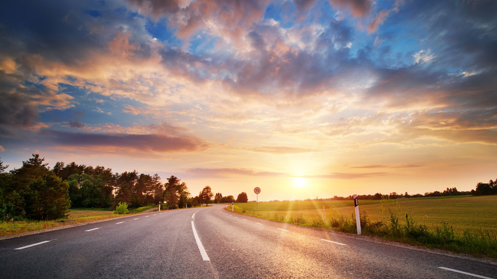 The sun rises over an open road