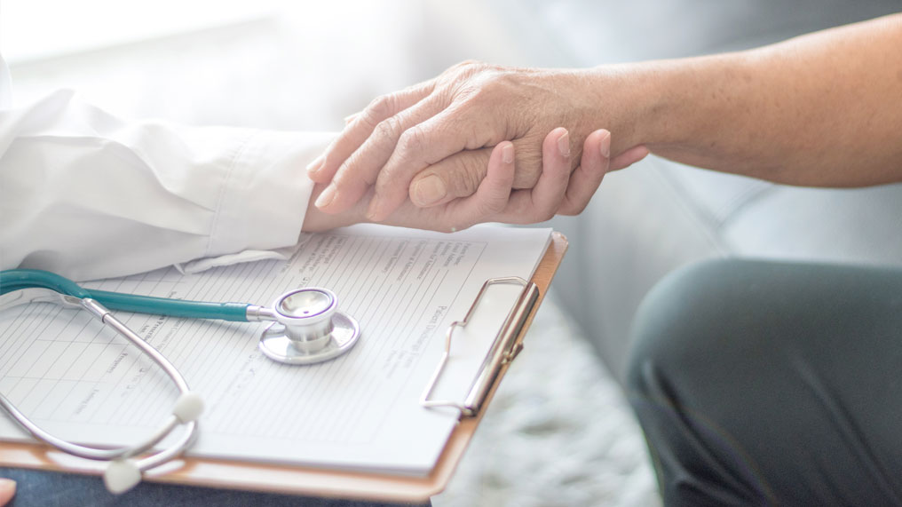 A doctor holds someone's hand in support.