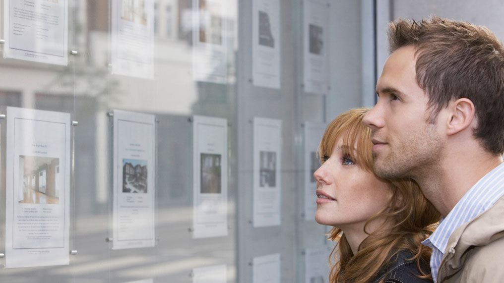 A couple stare at the homes listed in the window of an estate agent.