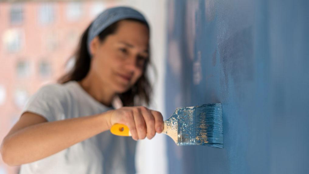A woman paints a wall blue.