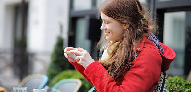 Young woman sitting outside a cafe, looking at her mobile phone
