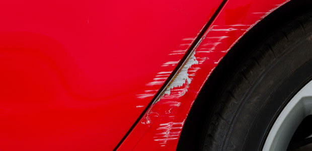 Superficial damage on a red car by wheel trim