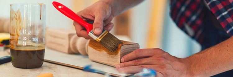 Man varnishing a piece of wood