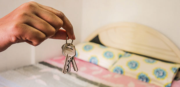 Hand holding house keys in bedroom