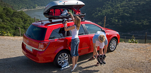 Young couple getting roller blades out of root top box on the side of a mountain